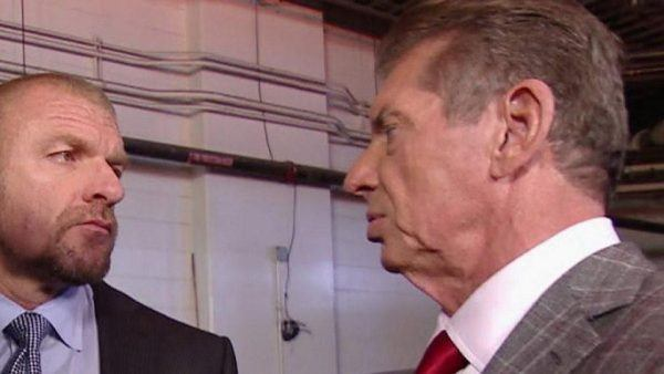 Triple H looking angrily at Vince McMahon